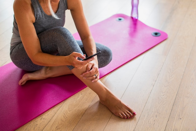 Fit девушка сидит на коврик для йоги с телефоном Бесплатные Фотографии