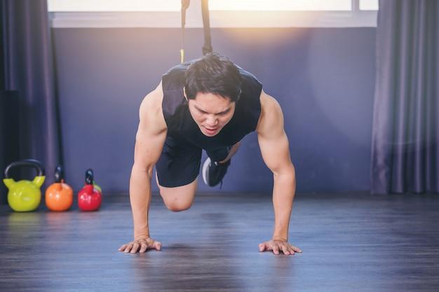Fit человек делает упражнения для спины позвоночника, отжимания с веревкой фитнес-ремни в тренажерном зале Premium Фотографии