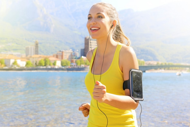 Fitness athlete woman running and wearing phone armband with touchscreen during cardio workout on lake. Premium Photo