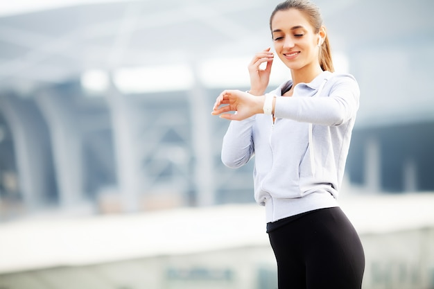 Fitness beautiful woman drinking water and listen to music after running Premium Photo