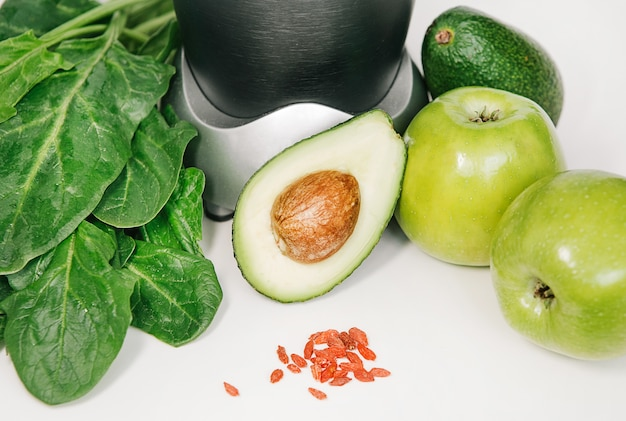 Fitness blender with a set of healthy products, apple avocado spinach Free Photo