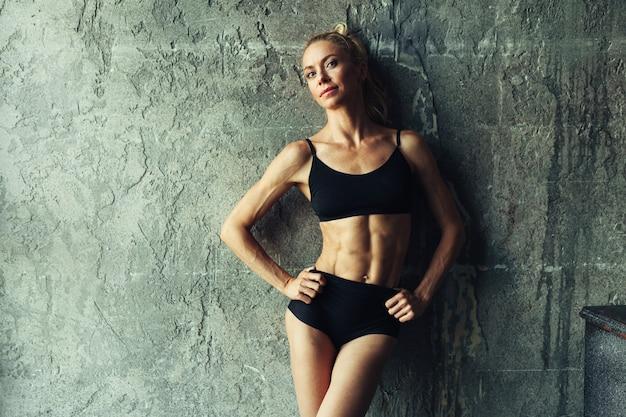 Fitness blondie woman standing near the wall Premium Photo