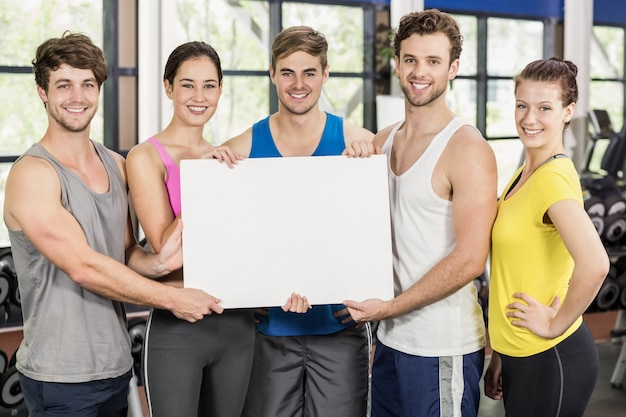 Fitness class holding a white card in gym Premium Photo