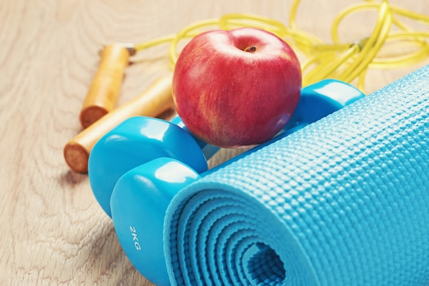 Fitness concept with a blue dumbbells and yoga mat Premium Photo