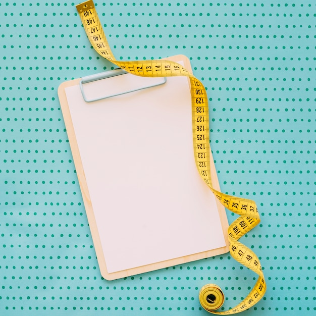 Fitness concept with tape measure on clipboard Premium Photo