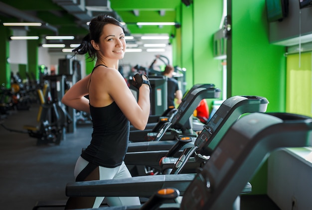 Fitness girl beautiful brunette running on treadmill morning. concept of a healthy lifestyle. Premium Photo