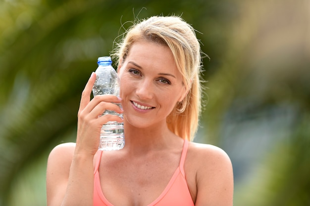 Fitness girl drinking water after exercising Premium Photo