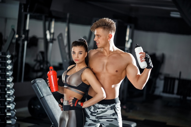 Fitness girl and guy model with a shaker relax in the gym. slim sporty woman and man in sportswear clothes Premium Photo