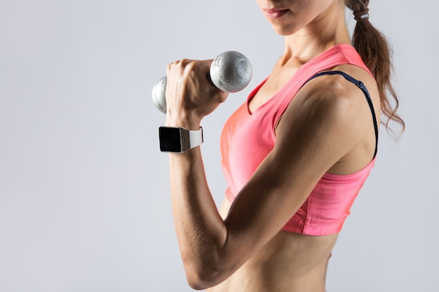 Fitness girl lifting dumbbell Free Photo