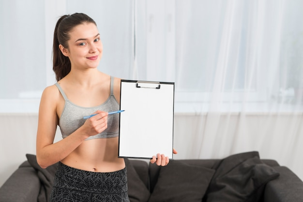 Fitness girl pointing at folder Free Photo