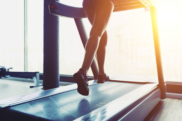 Fitness girl running on treadmill Free Photo