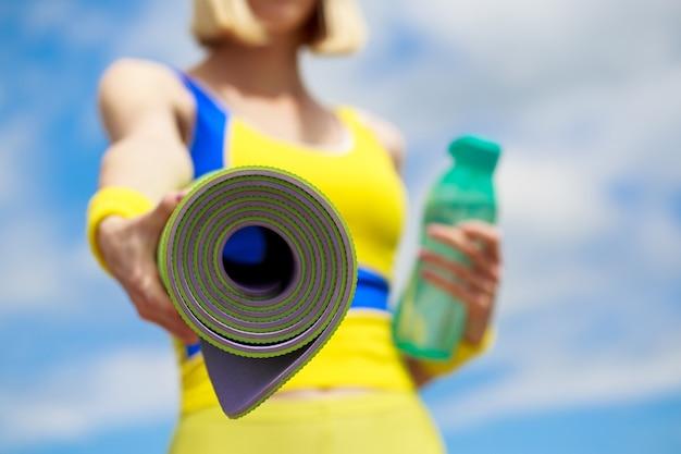 Девушка фитнеса с циновкой йоги над предпосылкой неба. женщина в спортивной одежде держит коврик для йоги и бутылку воды. Premium Фотографии