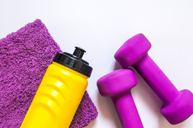 Fitness gym equipment. dumbbells with towel and wate bottler. workout footwear. sport trainers on white background. sport, healthy lifestyle and objects concept Free Photo