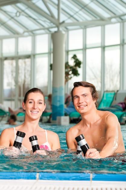 Fitness - gymnastics under water in swimming pool Premium Photo