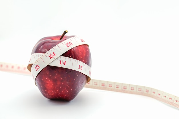 Fitness and health care concept. close up of apples with tape measure Premium Photo