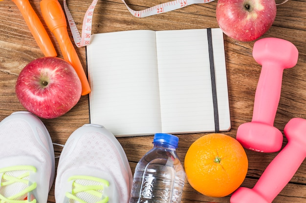 Fitness, healthy and active lifestyles concept, bottle of water, dumbbells, sport shoes, smartphone with headphone and apples on wood background. copy space for text. top view Free Photo