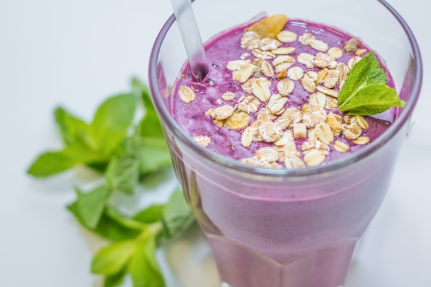 Fitness, healthy lifestyle concept. good for gym, sport, delicious berry fitness cocktail with oats, oatmeal with mint. yogurt and fruit for athletes. diet Premium Photo