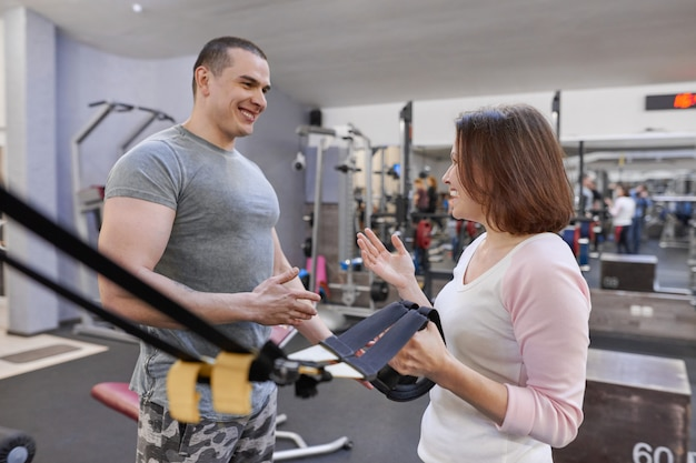 Fitness instructor and mature woman at gym. Premium Photo