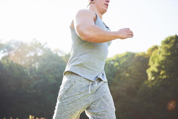 日没時に自然の中でジョギングするフィットネスマンアスリート。 無料写真