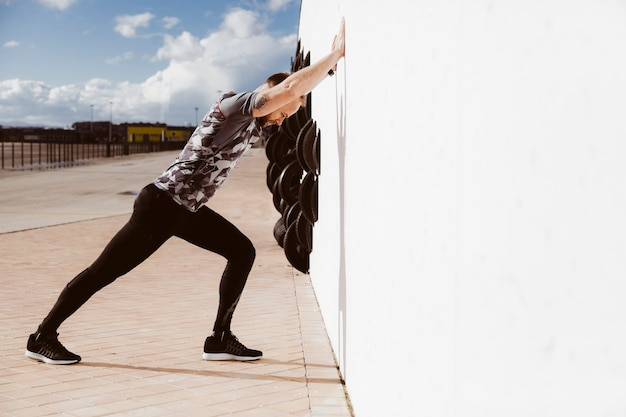 Fitness man doing push-ups against wall Free Photo