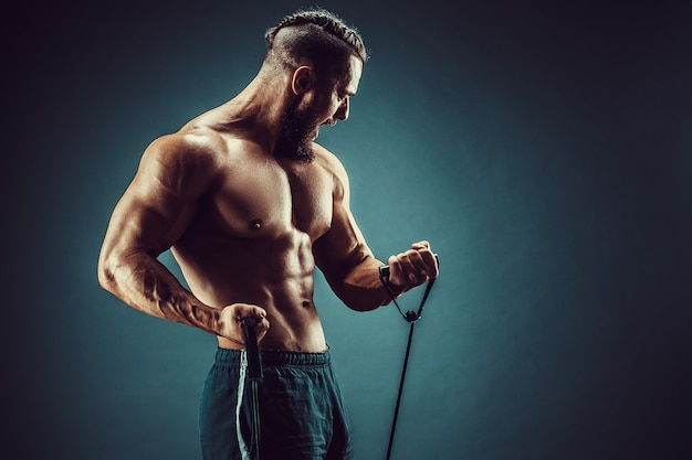 Fitness man exercising with stretching band. muscular sports man exercising with elastic rubber band. guy working out with rubber band. fit, fitness, exercise, workout and healthy lifestyle Premium Photo