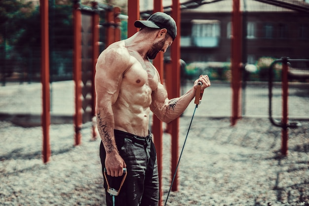 Fitness man exercising with stretching band in outdoor gym. Premium Photo