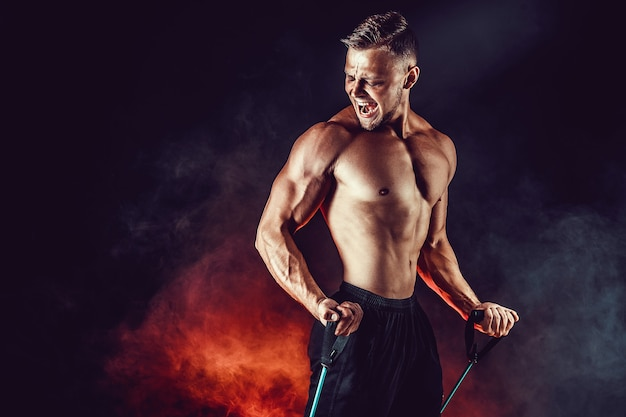 Fitness man exercising with stretching band in studio. Premium Photo