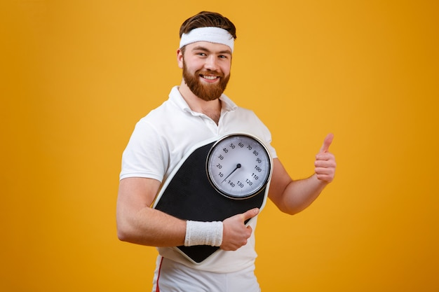 Fitness man holding weight scales and showing thumbs up Free Photo