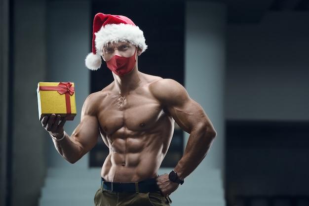 선물 상자와 체육관에서 산타 클로스 모자 의상에서 피트 니스 남자. 프리미엄 사진