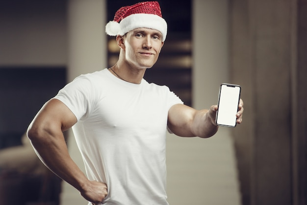 휴대 전화 체육관에서 산타 클로스 모자 의상에서 피트 니스 남자. 기쁜 성 탄과 새 해 개념 프리미엄 사진