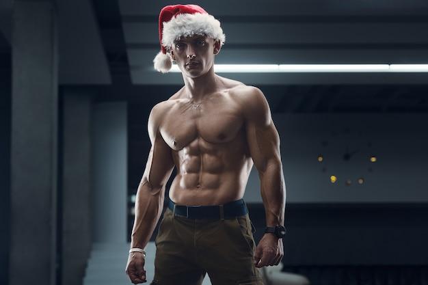 휴대 전화 체육관에서 산타 클로스 모자 의상에서 피트 니스 남자. 프리미엄 사진