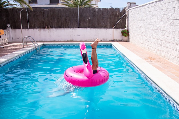 Fitness man jumping into the water in the pool in the center of inflatable flamingo a day of summer vacation Premium Photo