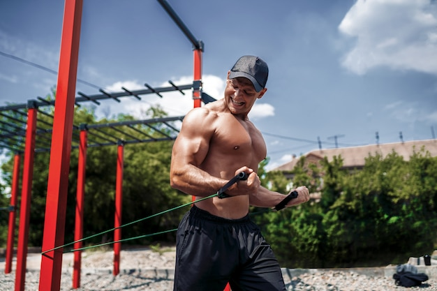 Fitness man training chest with resistance bands at street gym yard. outdoor workout. body workout with equipment outside. elastic rubber band accessory. Premium Photo
