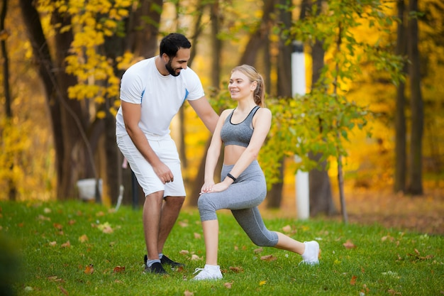 Fitness. personal trainer takes notes while woman exercising outdoor Premium Photo
