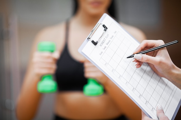 Fitness plan. sports trainer amounts to workout plan close-up Premium Photo