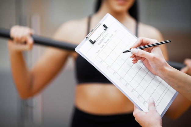 Fitness plan, sports trainer amounts to workout plan close-up Premium Photo