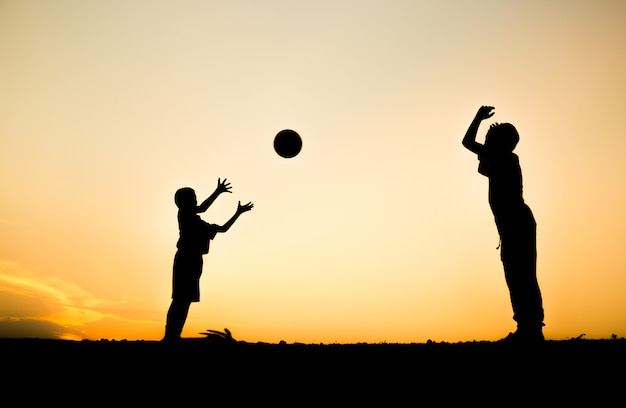 Wellness background  Fitness silhouette children throwing ball with sunrise background ...
