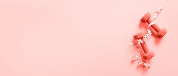 Fitness, sport concept with dumbbells and measuring tape over coral color background. Premium Photo