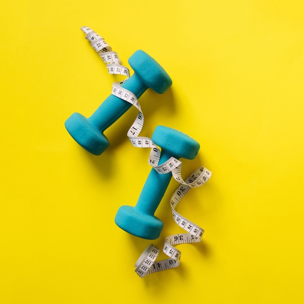 Fitness, sport concept with dumbbells and measuring tape over yellow background Premium Photo