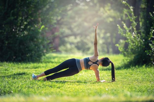 Fitness, sport lifestyle concept making yoga exercises on mats outdoors Premium Photo