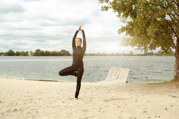 Fitness, sport, people and lifestyle concept - young woman making yoga exercises on beach Premium Photo