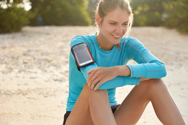 Fitness, sport, technology, people and exercising concept. pleased satisfied female wears pulsometer while trains outdoor over beach sunset background, works on her body, keeps fit and healthy Free Photo