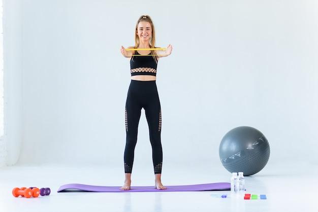 フィットネス、スポーツ、トレーニング、人々、ライフスタイルコンセプト-ジムでエキスパンダーやレジスタンスバンドで運動をしている女性 Premium写真