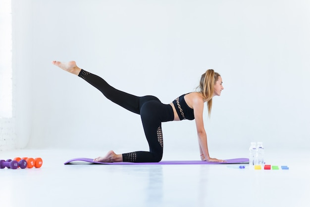 Fitness Sport Yoga And Healthy Lifestyle Concept Sporty Yoga Girl On The Beach Practices Backward Kicks Leaning On Her Hands Premium Photo