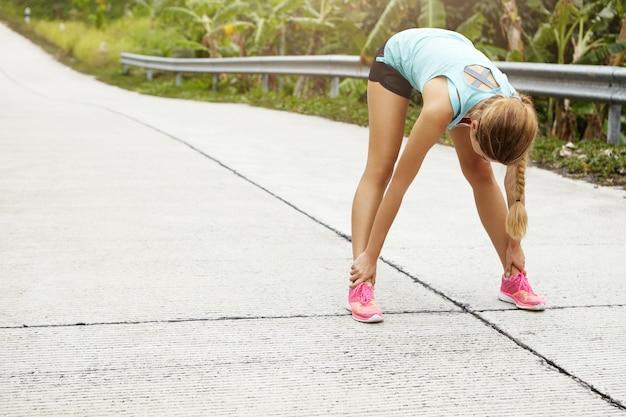 Фитнес, спорт, упражнения, люди и концепция образа жизни. белокурая спортсменка растяжения и наклоняется перед тренировкой на открытом воздухе. Бесплатные Фотографии