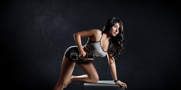 Fitness sports woman trains on a dark background Premium Photo