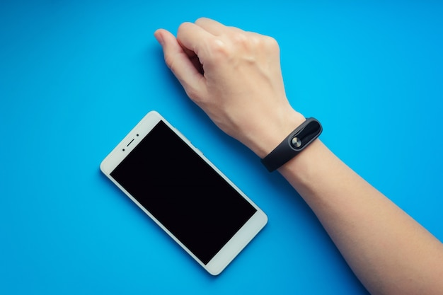 Fitness tracker on female hand on orange background and smartphone. Premium Photo