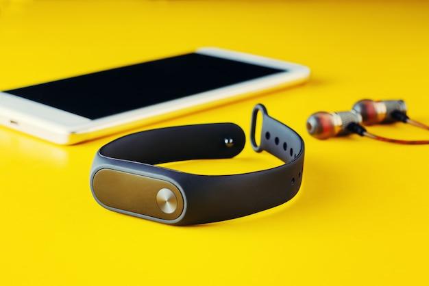 Fitness tracker, headphones and smartphone on yellow background Premium Photo