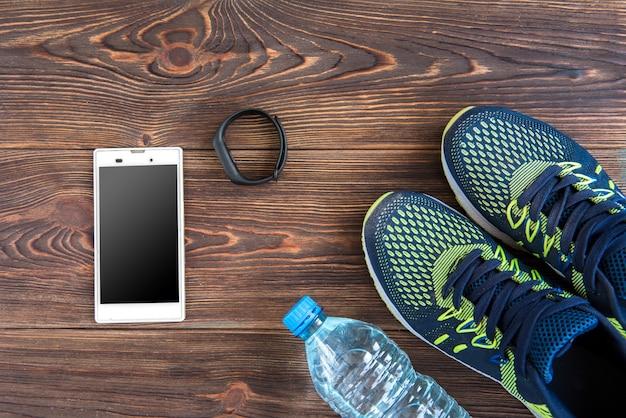 フィットネストラッカー、スマートフォン、スニーカー、コピースペース付きの木製テーブル。健康的なライフスタイルの背景。 Premium写真