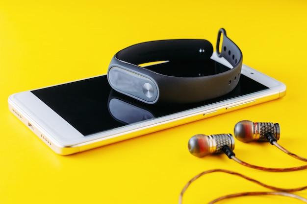 Fitness tracker, smartphone and headphones on yellow background Premium Photo